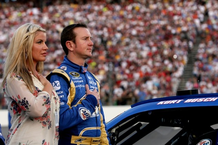 Kurt Busch stands with his wife Eva on the grid during the national anthem that was presented by The Commandant's Own United States Marine Drum & Bugle Corps. (Credit: Chris Trotman/Getty Images)