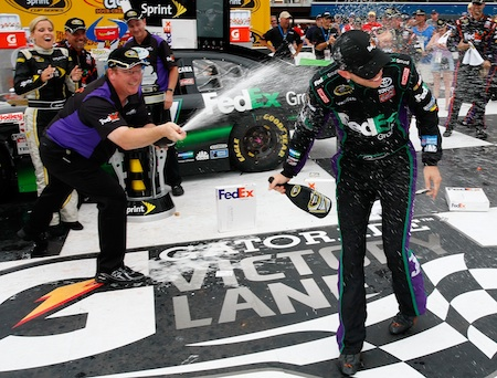 (Left to right) Crew chief Mike Ford sprays his driver Denny Hamlin in Michigan International Speedway's Victory Lane after winning the Heluva Good! Sour Cream Dips 400 Sunday in Brooklyn, Mich. (Credit: Geoff Burke/Getty Images for NASCAR)