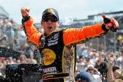 Jamie McMurray celebrates his Brickyard 400 victory at Indianapolis Motor Speedway. He became the third driver to win the Brickyard and the Daytona 500 in the same season. (Credit: John Harrelson/Getty Images for NASCAR)