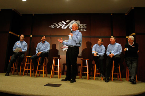 Team owner Joe Gibbs (center) speaks about the 20th anniversary of Joe Gibbs Racing, as (left to right) JGR President J.D. Gibbs, former JGR drivers Tony Stewart and Bobby Labonte, JGR senior vice president of racing operations Jimmy Makar and Interstate Batteries CEO Norm Miller look on during the NASCAR Sprint Media Tour hosted by Charlotte Motor Speedway, held at Joe Gibbs Racing, on Thursday in Huntersville, N.C. (Credit: Jason Smith/Getty Images for NASCAR)