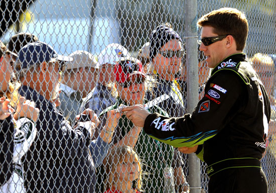 Carl Edwards signs autographs for fans after his qualifying lap Sunday at Daytona International Speedway in Daytona Beach, Fla. (Credit: Jerry Markland/Getty Images for NASCAR)