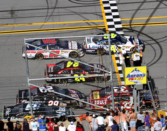 Fans watch Jimmie Johnson cross the finish line .002 seconds ahead of Clint Boywer at Talladega Superspeedway. Johnson's win ties the record for closest finish in NASCAR history. (Credit: Jerry Markland/Getty Images for NASCAR)