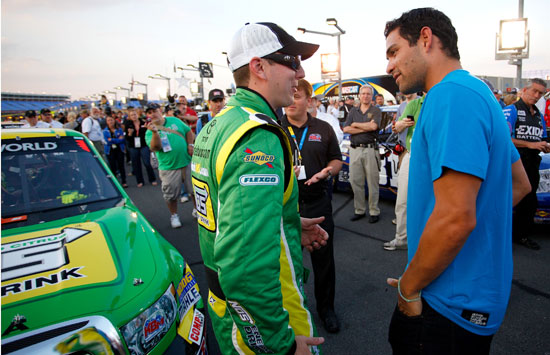 New York Jets quarterback Mark Sanchez talks with Kyle Busch on the grid before the start of the North Carolina Education Lottery 200 at Charlotte Motor Speedway (Credit: Jeff Zelevansky/Getty Images for NASCAR)