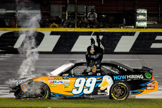 Carl Edwards does his trademark victory backflip after tearing up his car sliding through the infield grass at Charlotte Motor Speedway. (Credit: Jared C. Tilton/Getty Images for NASCAR)