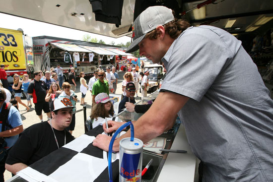 Travis Pastrana signs autographs for fans during practice for the NASCAR Sprint Cup Series Crown Royal Presents The Matthew and Daniel Hansen 400 at Richmond International Raceway on Apr. 29 in Richmond, Va. (Credit: Jerry Markland/Getty Images)