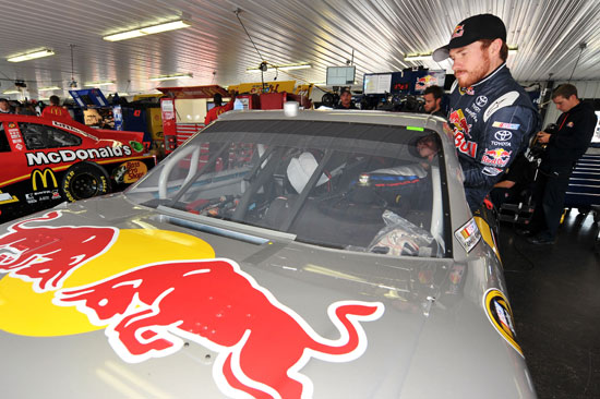 Brian Vickers, driver of the No. 83 Red Bull Toyota, climbs into his car in the garage area during practice for the NASCAR Sprint Cup Series 5-Hour Energy 500 at Pocono Raceway on June 10 in Long Pond, Pa. (Credit: Drew Hallowell/Getty Images for NASCAR)