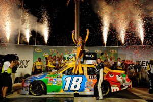 Kyle Busch climbs out of the No. 18 M&Ms in victory lane after winning the Quaker State 400 at Kentucky Speedway. (Credit: Jared C. Tilton/Getty Images for NASCAR)