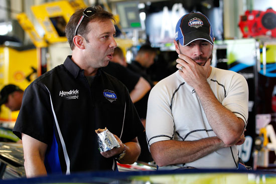 NASCAR Sprint cup Series No. 48 Lowe's Chevrolet crew chief Chad Knaus (left) talks with driver Jimmie Johnson (right) in the garage during the testing session at the NASCAR Sprint Cup Series at Kentucky Speedway on July 7 in Sparta, Ky. The No. 48 Hendrick Motorsports team was the fastest in this session. (Credit: Geoff Burke/Getty Images for NASCAR)