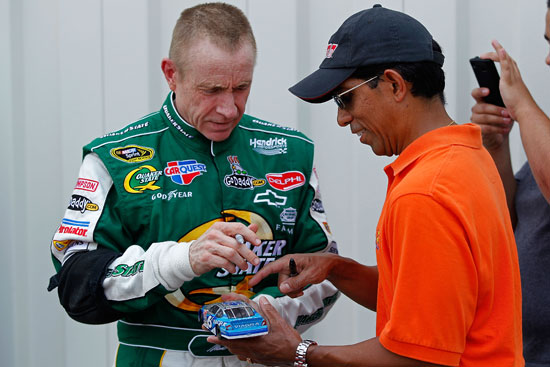 Mark Martin, driver of the No. 5 Quaker State/GoDaddy.com Chevrolet, signs his autograph for a fan in the garage during testing for the NASCAR Sprint Cup Series at Kentucky Speedway on July 7 in Sparta, Ky. (Credit: Geoff Burke/Getty Images for NASCAR)