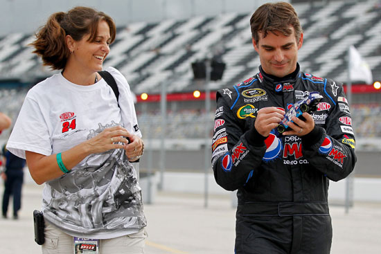 Jeff Gordon (R), driver of the #24 Pepsi MAX Chevrolet, signs an autograph for a fan in the garage area prior to practice for the NASCAR Sprint Cup Series COKE ZERO 400 Powered by Coca-Cola at Daytona International Speedway on June 30, 2011 in Daytona Beach, Florida. (Credit: Geoff Burke/Getty Images for NASCAR)