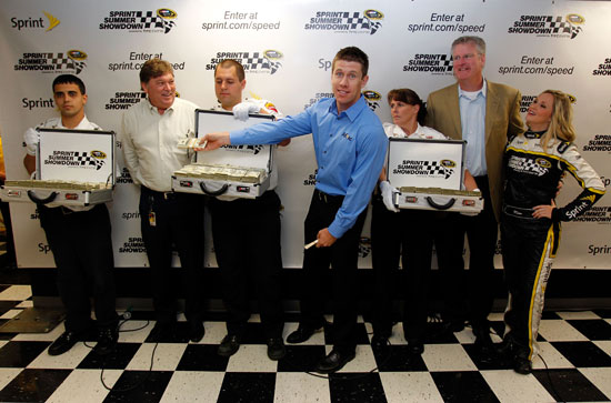 Flanked by Brinks security guards with three $1 million suitcases, (left to right) Robin Pemberton, NASCAR Vice President of Competition; Carl Edwards, driver of the No. 99 Aflac Ford Fusion; Tim Considine, director of sports marketing for Sprint; and Miss Sprint Cup Kim Coon announce the Sprint Summer Showdown presented by HTC EVO 3D on Sunday at New Hampshire Motor Speedway. (Credit: Geoff Burke/Getty Images for Sprint)