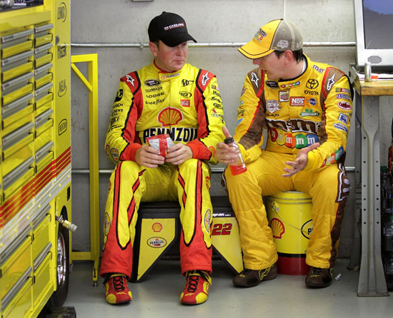 Kurt Busch (left), driver of the No. 22 Shell/Pennzoil Dodge, talks with his brother, Kyle Busch (right), driver of the No. 18 M&M's Toyota, during practice for the NASCAR Sprint Cup Series Brickyard 400 at Indianapolis Motor Speedway on July 29 in Indianapolis, Ind. (Credit: Jerry Markland/Getty Images for NASCAR)