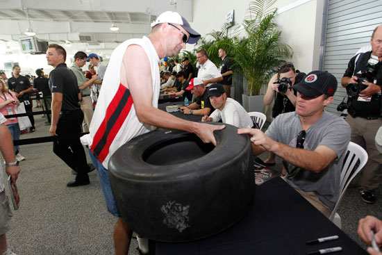 Kevin Harvick, driver of the No. 29 Budweiser Chevrolet autographs a tire for a race fan at the largest 2011 NASCAR Sprint Cup Series autograph session held at Indianapolis Motor Speedway on July 30 in Indianapolis, Ind. (Credit: Getty Images for NASCAR)