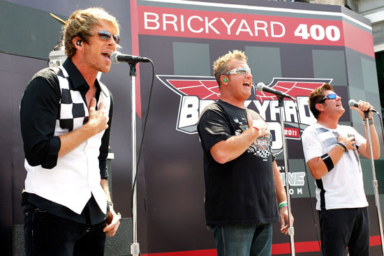 Joe Don Rooney (left), Gary LeVox (middle) and Jay DeMarcus (right) of Rascal Flatts perform prior to the NASCAR Sprint Cup Series Brickyard 400 at Indianapolis Motor Speedway on July 31 in Indianapolis, Ind. (Credit: Geoff Burke/Getty Images for NASCAR)