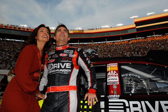 Five-time NASCAR Sprint Cup Series champion Jeff Gordon and wife Ingrid Vandebosch enjoy the prerace ceremony before the NASCAR Sprint Cup Series Irwin Tools Night Race at Bristol Motor Speedway on Saturday. (Credit: Jason Smith/Getty Images for NASCAR)