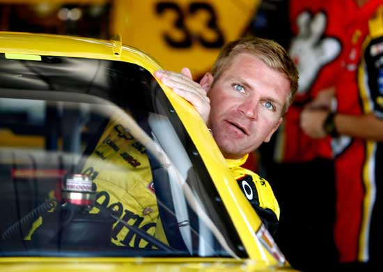 Clint Bowyer, driver of the No. 33 Cheerios/Hamburger Helper Chevrolet, climbs in his car in the garage during practice for the NASCAR Sprint Cup Series Pure Michigan 400 at Michigan International Speedway on Aug. 19 in Brooklyn, Mich. (Credit: Jeff Zelevansky/Getty Images for NASCAR)