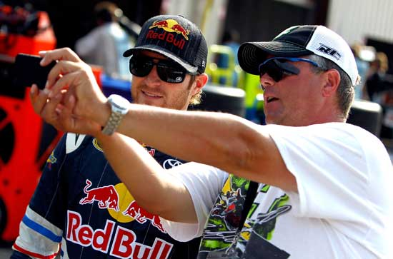 A fan takes a photo with Kasey Kahne (left), driver of the No. 4 Red Bull Toyota, during practice for the NASCAR Sprint Cup Series Pure Michigan 400 at Michigan International Speedway on Aug. 20 in Brooklyn, Mich. (Credit: Jeff Zelevansky/Getty Images for NASCAR)