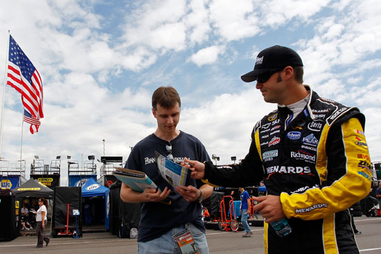 Paul Menard, driver of the No. 27 CertainTeed/Menards Chevrolet, signs autographs during practice for the NASCAR Sprint Cup Series Good Sam RV Insurance 500 at Pocono Raceway on Aug. 5 in Long Pond, Pa. Menard won the Brickyard 400 a week ago at Indianapolis Motor Speedway. (Credit: Geoff Burke/Getty Images for NASCAR)