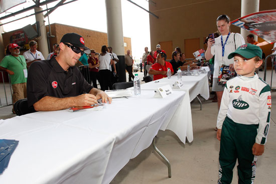 NASCAR Sprint Cup Series driver Kevin Harvick signs an autograph for a young fan at Atlanta Motor Speedway on Sept. 2 in Hampton, Ga. (Credit: By Geoff Burke/Getty Images for NASCAR)