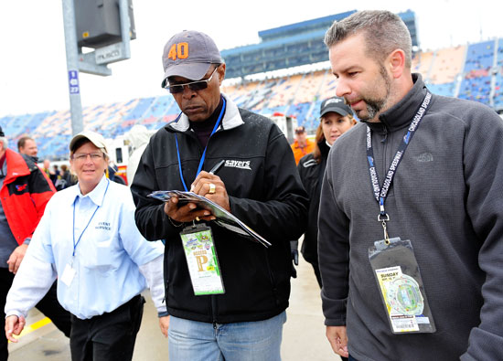 Former NFL player Gale Sayers (center) signs autographs for fans prior to the NASCAR Sprint Cup Series GEICO 400 at Chicagoland Speedway on Sept. 18 in Joliet, Ill. Sayers NFL career records include most touchdowns in a rookie season (22 in 1965), most touchdowns in a game (6, tied with Nevers and Jones), and highest career kickoff return average (30.56). (Credit: Rainier Ehrhardt/Getty Images for NASCAR)