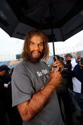 The GEICO Caveman, who will serve as Grand Marshal, walks out on the grid as rain falls prior to the NASCAR Sprint Cup Series GEICO 400 at Chicagoland Speedway on Sept. 18 in Joliet, Ill. (Credit: Jason Smith/Getty Images)