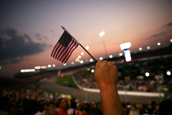 From laps 9-11, fans honor the 10th anniversary of the 9/11 terrorist attacks, staying silent for three circuits and waving American flags on Saturday at Richmond International Raceway. (Credit: Tom Pennington/Getty Images)