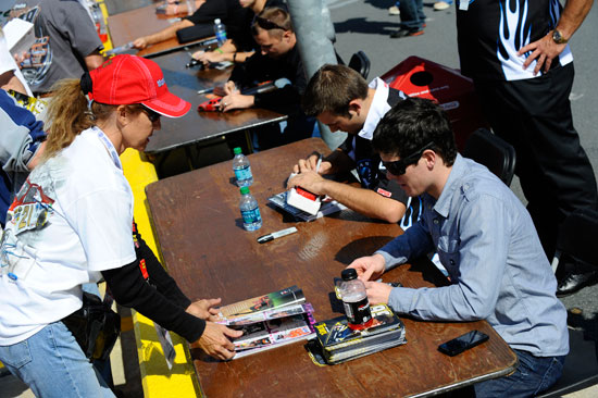 Ryan Truex (right) and Casey Roderick (left) sign autographs for a fan during the NASCAR Nationwide Series autograph session on Oct. 14 at the Charlotte Motor Speedway in Concord, N.C. (Credit: Jason Smith/Getty Images for NASCAR)