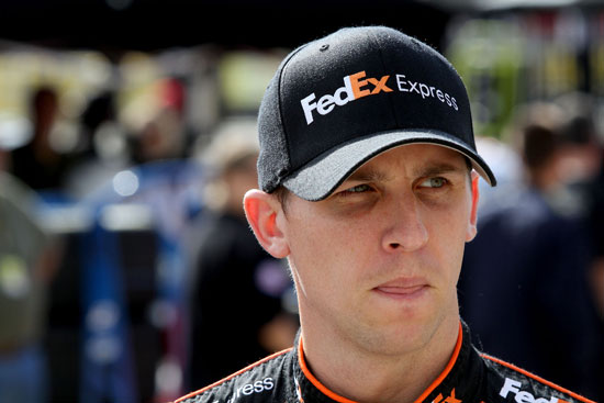 Denny Hamlin, driver of the No. 11 FedEx Express Toyota, walks in the garage area during practice for the NASCAR Sprint Cup Series Bank of America 500 at Charlotte Motor Speedway on Oct. 13 in Concord, N.C. (Credit: Jerry Markland/Getty Images for NASCAR)