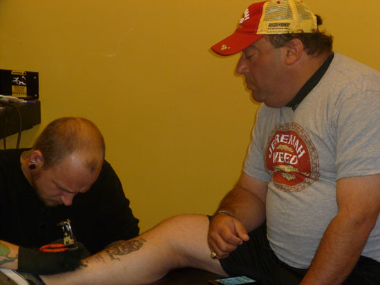 Matt Kenseth's spotter, Mike Calinoff, looks on as he gets his own tattoo courtesy of Jeremiah Weed