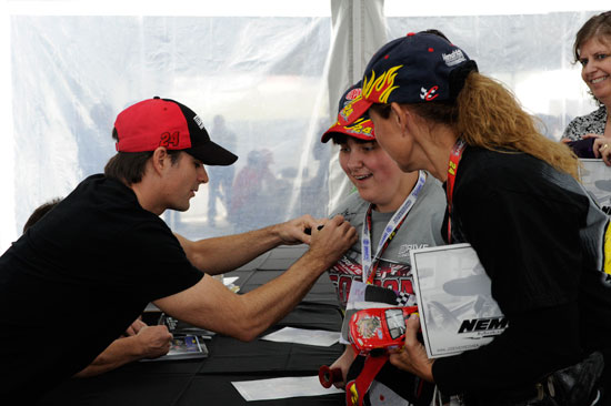 NASCAR Sprint Cup Series driver Jeff Gordon, No 24 Drive to End Hunger Chevrolet, signs autographs for a couple of fans at Charlotte Motor Speedway on Oct. 13 in Concord, N.C. (Credit: John Harrelson for Getty Images)