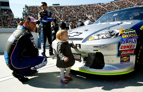 No. 48 crew chief Chad Knaus spends time with Genevieve Marie Johnson, the daughter of his driver five-time NASCAR Sprint Cup Series champion Jimmie Johnson, before the TUMS Fast Relief 500 at Martinsville Speedway on Sunday. (Credit: Jeff Zelevansky/Getty Images for NASCAR)