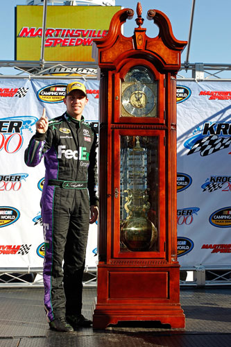Denny Hamlin celebrates with his Grandfather Clock for winning the NASCAR Camping World Truck Series Kroger 200 at Martinsville Speedway on Saturday.(Credit: Geoff Burke/Getty Images for NASCAR)