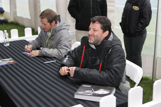 (Left to right) J.J. Yeley and Tony Stewart sign autographs for fans at Martinsville Speedway on Friday. (Credit: Tom Whitmore/Getty Images for NASCAR)