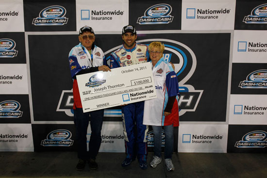 Elliott Sadler poses with Joseph Thornton and wife, winners of $100,000 in the NASCAR Nationwide Dash 4 Cash giveaway. (Credit: Geoff Burke/Getty Images for NASCAR)