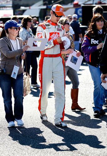 Joey Logano, driver of the No. 20 The Home Depot Toyota, signs autographs during practice for the NASCAR Sprint Cup Series Good Sam Club 500 at Talladega Superspeedway on Oct. 21 in Talladega, Ala. (Credit: Jeff Zelevansky/Getty Images for NASCAR)