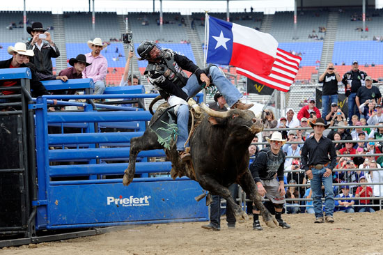 "NASCAR TV commentator and former driver Kyle Petty rides a bull during a bull riding exhibition at the ""No Limits"" Garage Party presented by WinStar World Casino at Texas Motor Speedway on Nov. 6, 2011, in Fort Worth, Texas. (Credit: John Harrelson/Getty Images for NASCAR)"