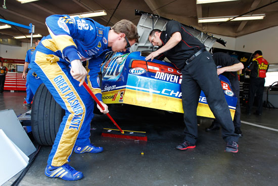 Brad Keselowski lends a hand to his Penske Racing team by sweeping under his No. 2 Miller Lite Dodge in the Daytona International Speedway garage. (Credit: Streeter Lecka/Getty Images)