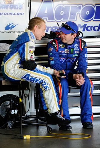Mark Martin, driver of the No. 55 Aaron's Dream Machine Toyota, talks to Kyle Busch, driver of the No. 18 Snickers Toyota, in the garage area during practice for the NASCAR Sprint Cup Series Series Quicken Loans 400 at Michigan International Speedway on Friday in Brooklyn, Mich. (Credit: John Harrelson/Getty Images for NASCAR)