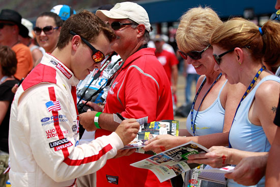 Trevor Bayne, driver of the No. 21 Motorcraft/Quick Lane Tire & Auto Center Ford, signs autographs during qualifying for the NASCAR Sprint Cup Series Quicken Loans 400 at Michigan International Speedway on Saturday in Brooklyn, Mich. (Credit: Geoff Burke/Getty Images for NASCAR)