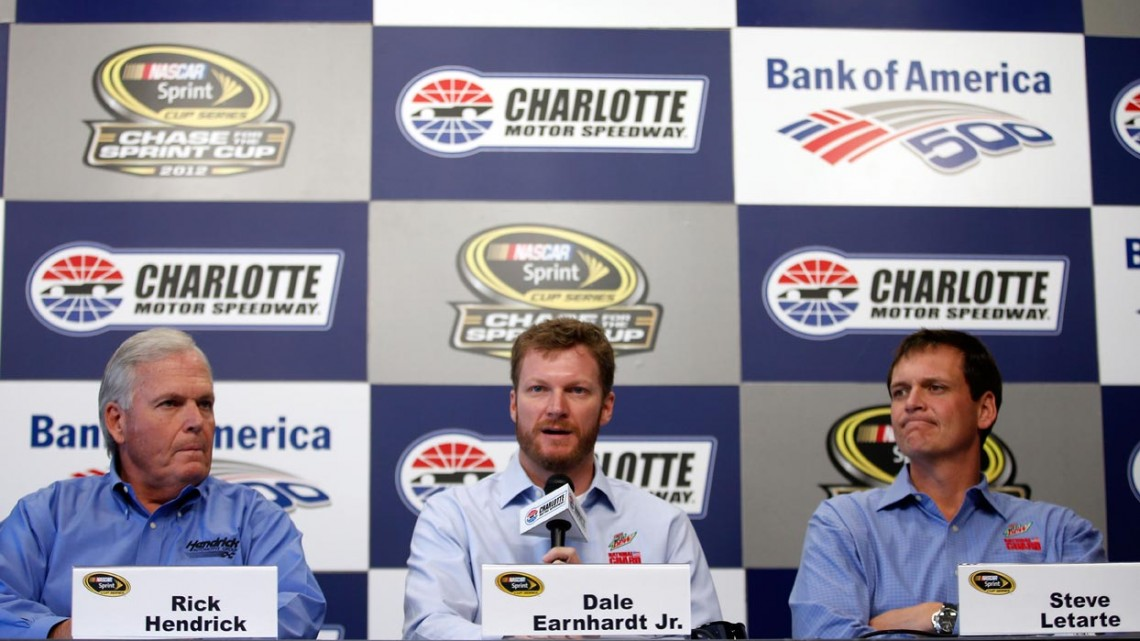 Dale Earnhardt Jr. (center), driver of the No. 88 Diet Mountain Dew Chevrolet, is flanked by Hendrick Motorsports team owner Rick Hendrick (left) and crew chief Steve Letarte (right) as he speaks to the media at Charlotte Motor Speedway on Oct. 11 in Charlotte, N.C. Earnhardt will miss two races after suffering a concussion from an accident in Talladega last week. (Credit: Chris Graythen/Getty Images)